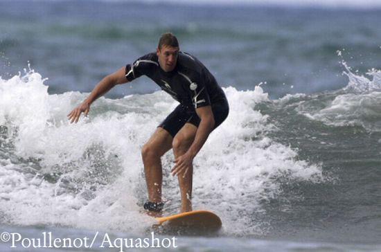 Alain Bernard en action sur une planche de surf.