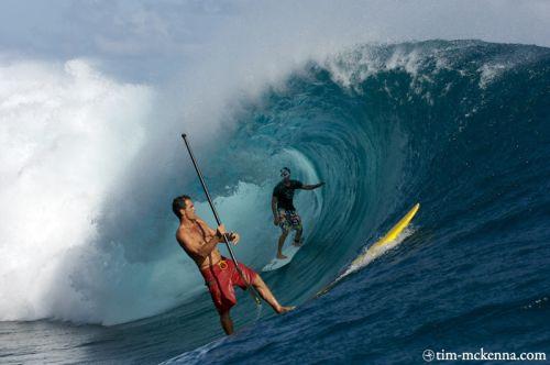 Poto retourne au pic à Teahupoo sur son SUP sous l'oeil incrédule d'un surfeur dans le barrel.
