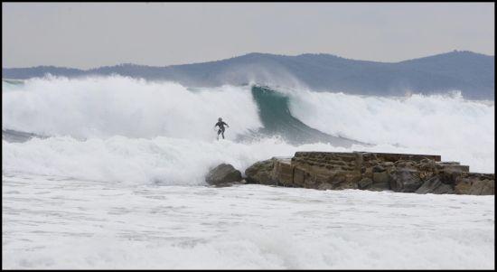 Boris surfant de grosses vagues en Méditerranée avec les rochers en ligne de mire…