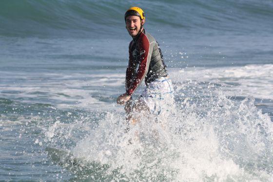 Boris heureux de surfer avec un casque pour protéger sa tête d'un traumatisme crânien