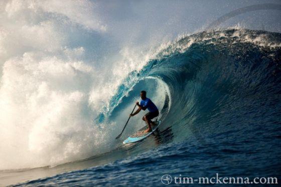 Vetea David dit Poto dans un énorme tube à Teahupoo en SUP (stand up paddle) : photo par Tim Mc Kenna.
