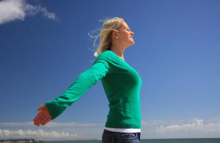 Jeune femme respirant à pleins poumons l'air marin sur la plage, la respiration abdominale est bénéfique pour la santé / iStockphoto