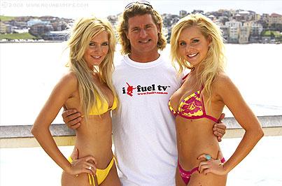 Le surfeur Mark Occhiluppo entouré de deux surfeuses blondes en bikini, Occy est le playboy du surf et le tombeur de ces dames !