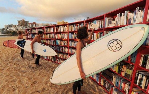Surfeurs lisant des livres sur la plage de Bondi Beach avec leur planche de surf sous le bras