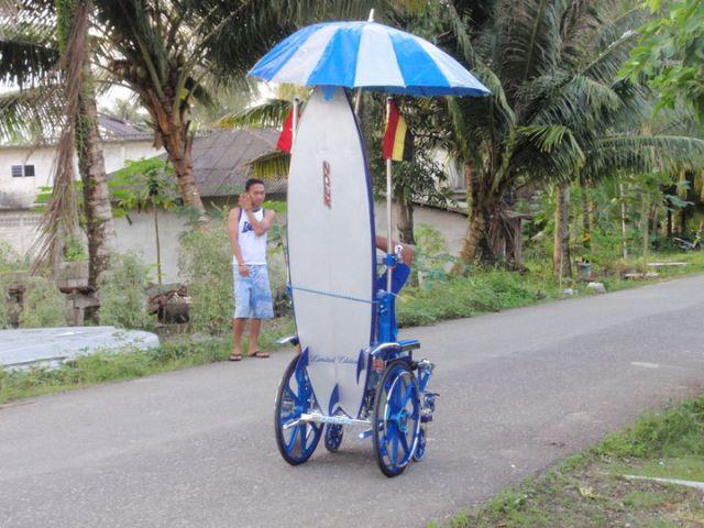 """Deddy """"surfwheelchair"""" Dachi va surfer à la plage en fauteuil roulant avec parasol incorporé."""