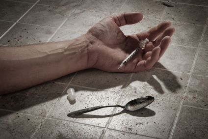 Toxicomane au sol avec une seringue dans la main et une cuillere dans de mauvaises conditions d'hygiene. Ne vaudrait-il pas mieux des salles de shoot  iStockphoto_ Daniel Loiselle