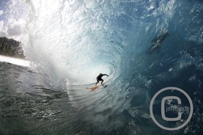 Le surfeur Jamie Sterling bien profond dans le tube avec un casque