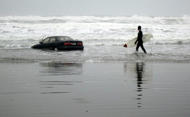 Femme au volant, voiture dans les vagues au tournant…