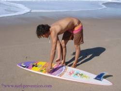 Mauvaise posture pour ramasser sa planche en courbant le dos jambes tendues.
