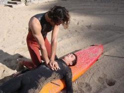 Un longboard peut faire office de plan dur pour effectuer des compressions thoraciques sur le sable. Copyright Surf Prévention.