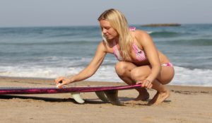 Coline Ménard montre comment waxer un longboard. Photo Laurent Masurel.